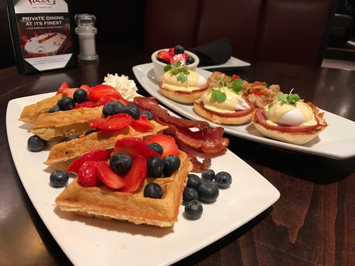 waffles with strawberry and bluebarries garnishes on a plate and eggs benedict meal on a plate