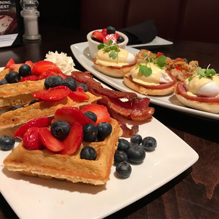 Waffles on a plate with strawberries and blueberries on top, plate of eggs benedict in the background
