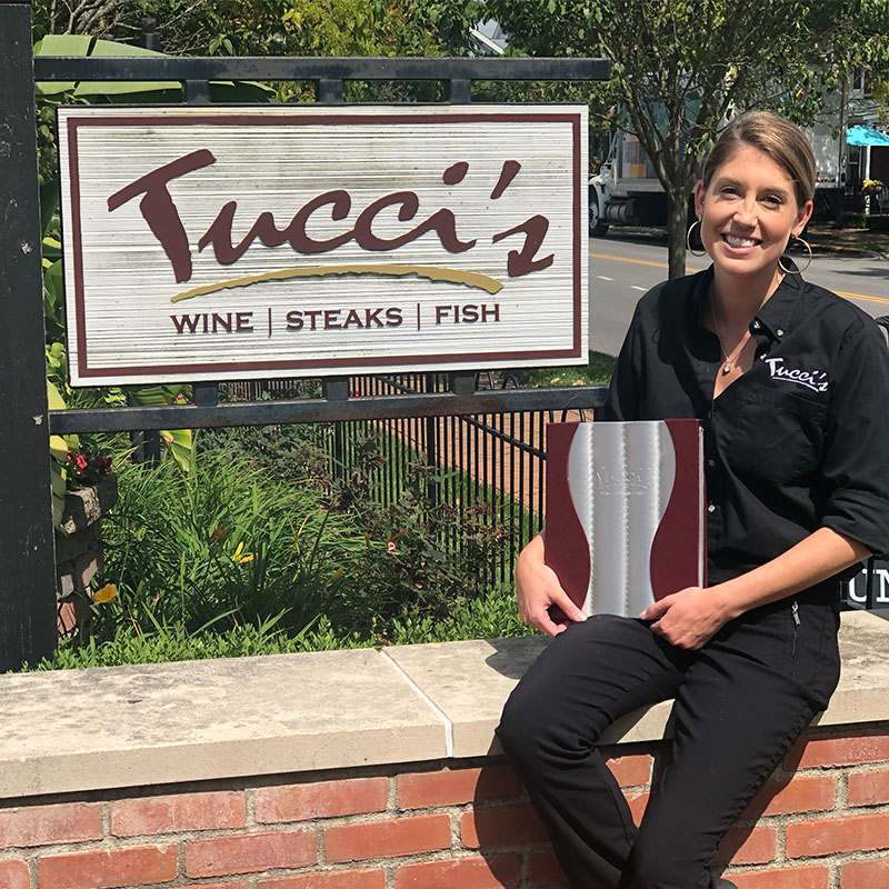 Employees holding menu sitting outside in front of the Tucci's sign, smiling