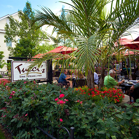 Outdoor patio area with guests sitting at tables and Tucci's sign in front