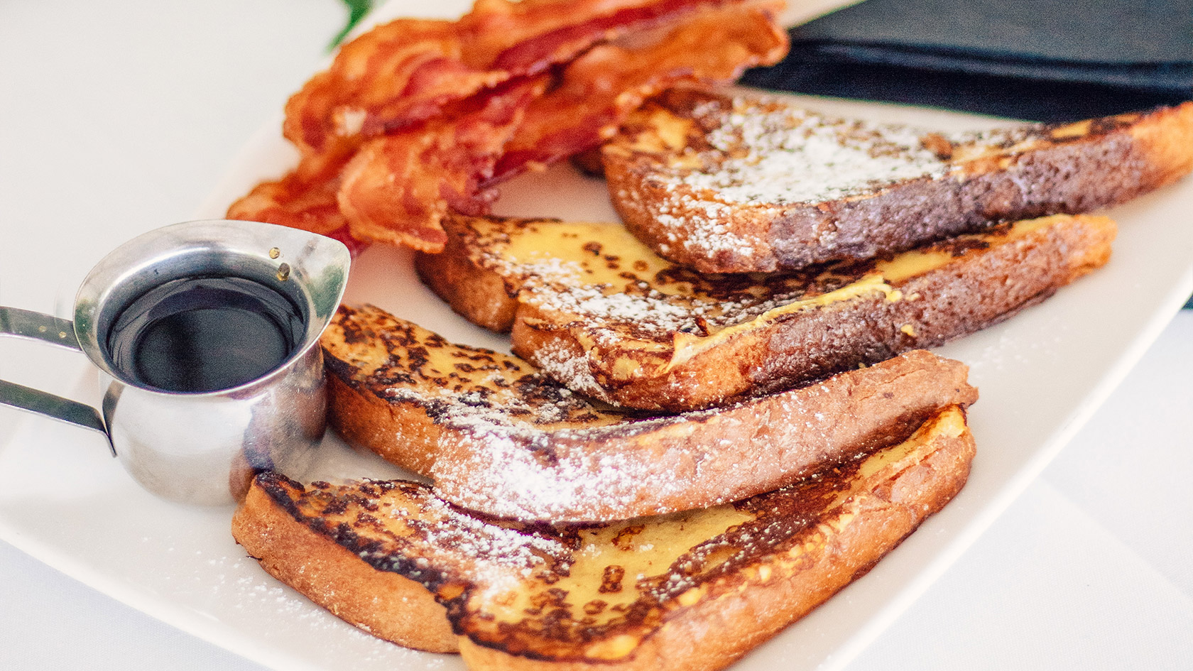French toast on a plate with bacon on the si