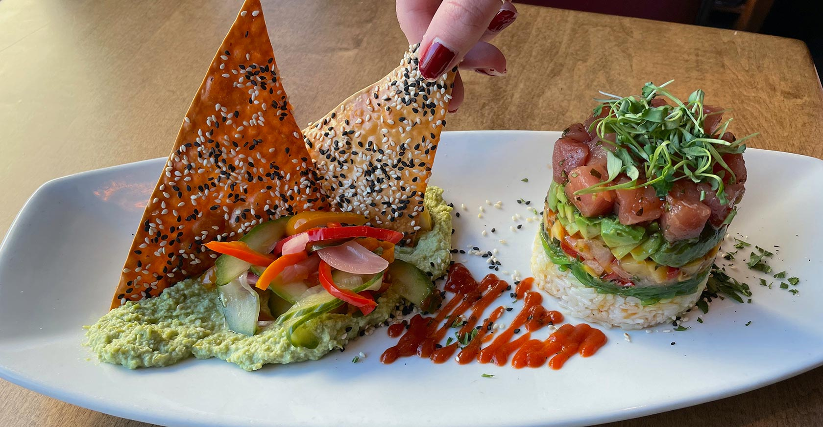 Woman's hand picking up sesame cracker from raw tuna entree dish