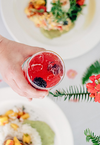 Hand holding a cocktail in a glass over a table of plated food dishes