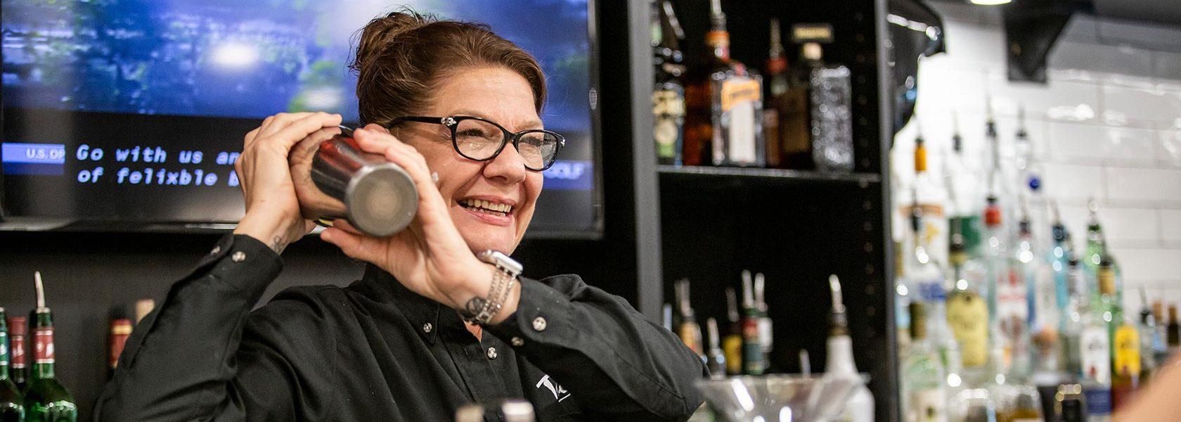 Bar chef shaking cocktail shaker over her shoulder