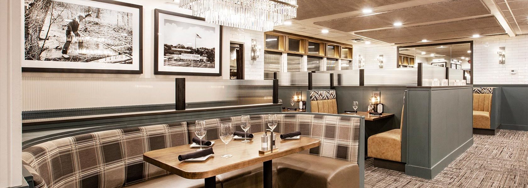 Open dining room area with booth seating and black and white large photography on walls.