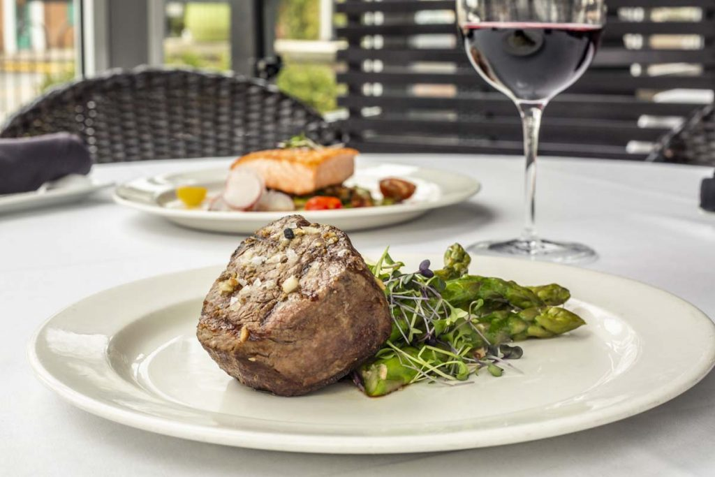 Piece of filet mignon steak plated with asparagus, glass of red wine in background