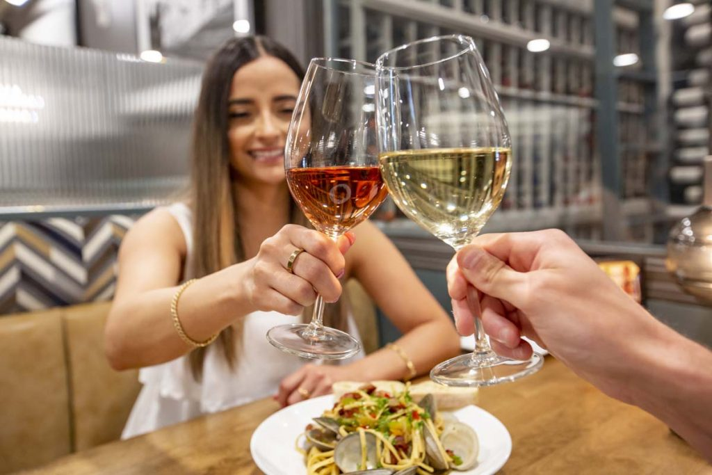 Woman clicking glass of wine with her guest.