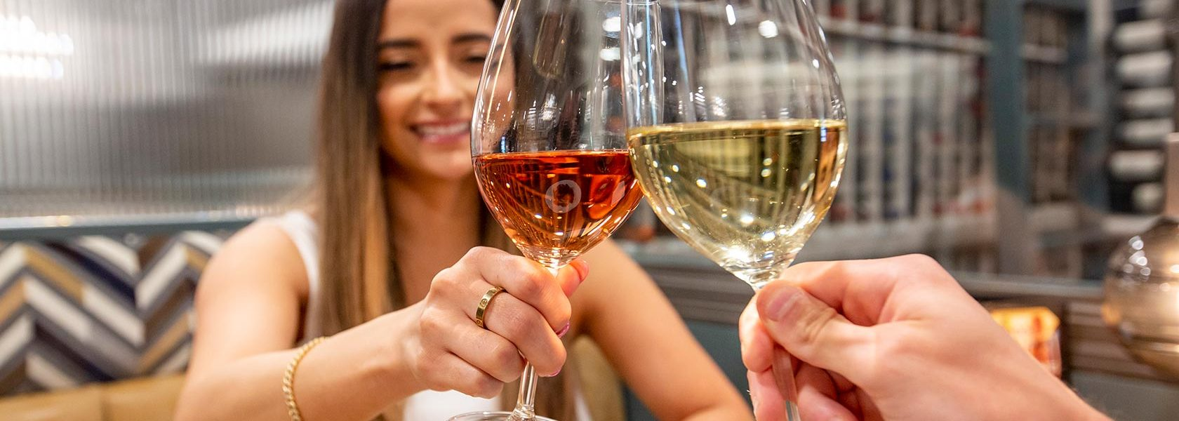 Woman clinking wine glasses in toast with dining companion.