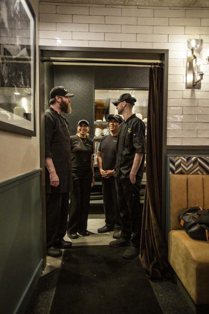 Executive chef and kitchen team standing in kitchen doorway talking.