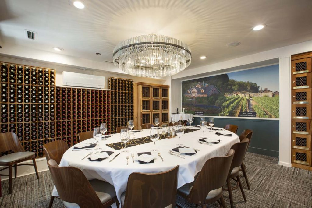 Private dining room with wine cellar on one wall and service set for 12 on center table