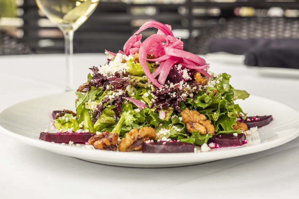 Tucci's salad topped with pickled red onion with white wine in background