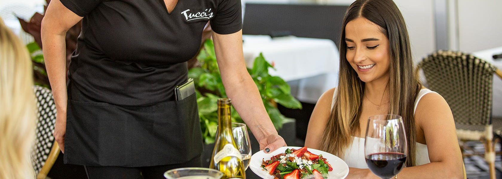 Woman being served a salad in light outdoor seating area.