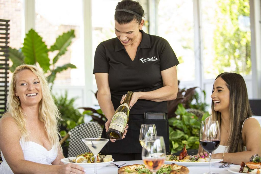 Tucci's server presents wine bottle to guest for approval