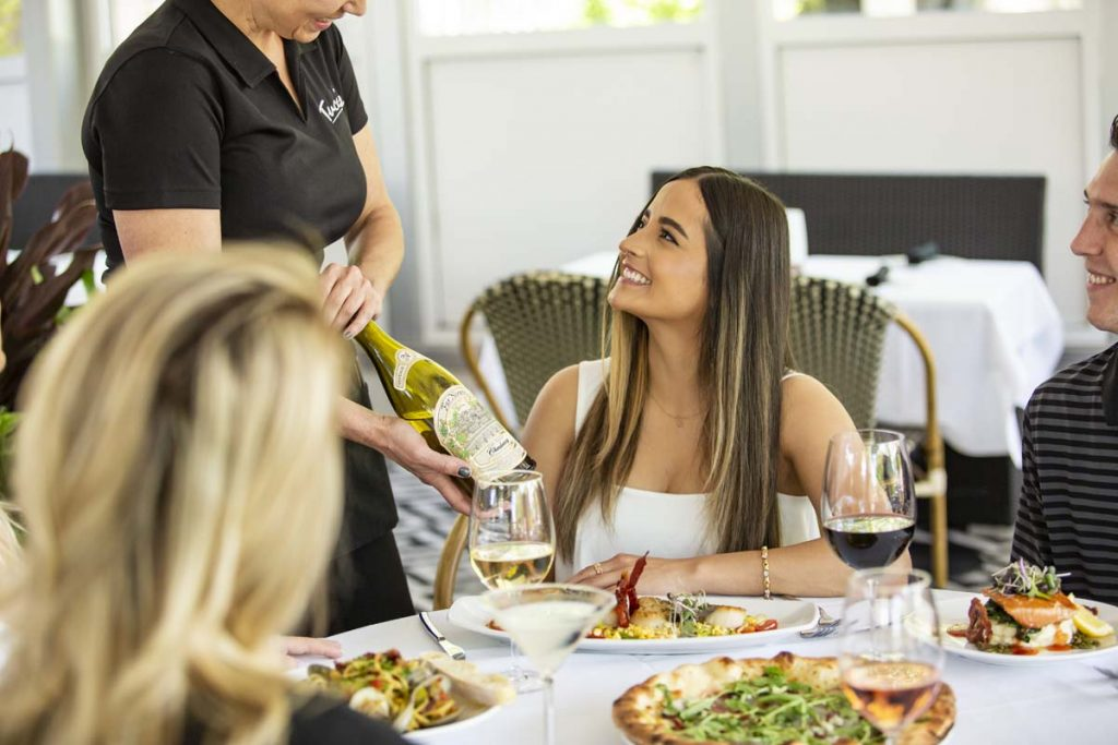 Female guest smiles as wine is presented by server