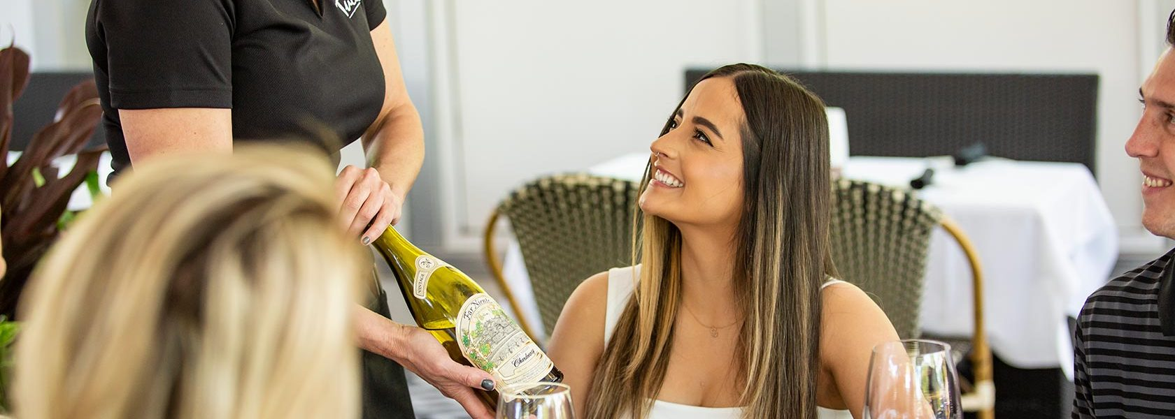 Woman smiling at server presenting bottle of wine